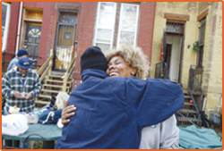 Photo of a housing advocate hugging a client who has been successful in maintaining her housing.