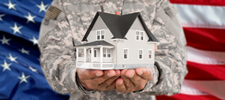 American flag background with person in uniform holding a house
