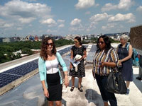 NHT's Kathleen Berube leads Summit attendees through a rooftop solar array on top of Channel Square Apartments.