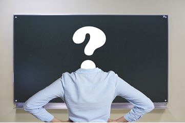 Person with a question mark looking at a chalkboard