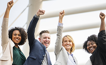 coworkers raising their hands in the air to celebrate success