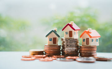 Piles of change with houses on top