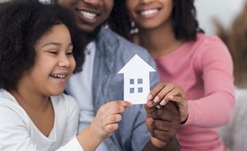 Family smiling and holding paper cutout of a house together