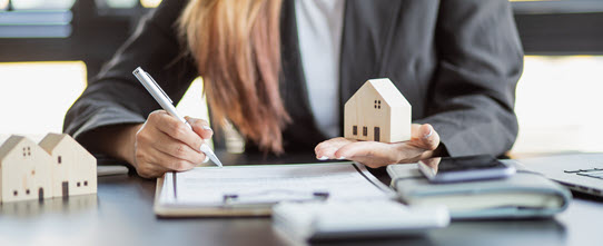 Business woman signing a document and holding a model of a house in her hand