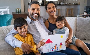 Family sitting on a couch holding up a picture their kids drew of a house and family