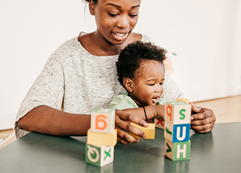 Mother and baby playing with blocks