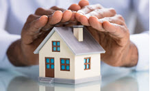Person covering a house model with hands