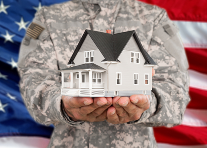 Veteran in uniform in front of the US flag holding a model house