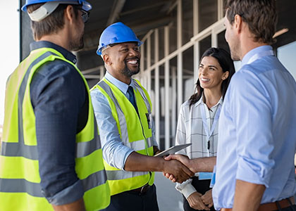 Construction worker shaking hands with office worker