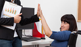 two women high fiving at desk